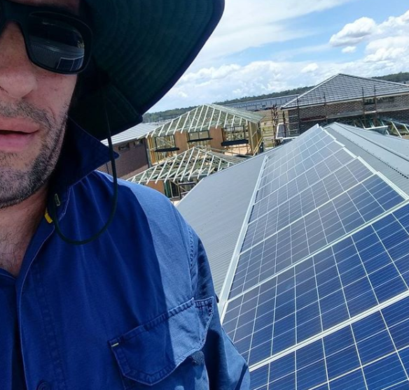 Solar Electrician on roof with solar panels