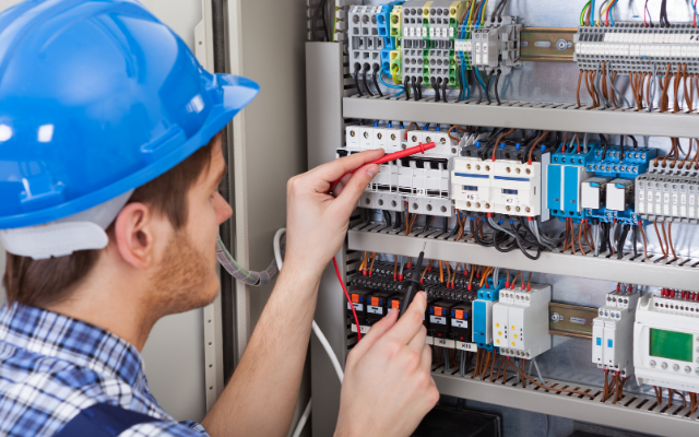 Electrician working on electrical switchboard