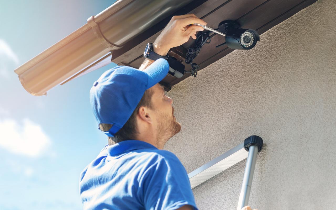 Tradesman installing a security camera