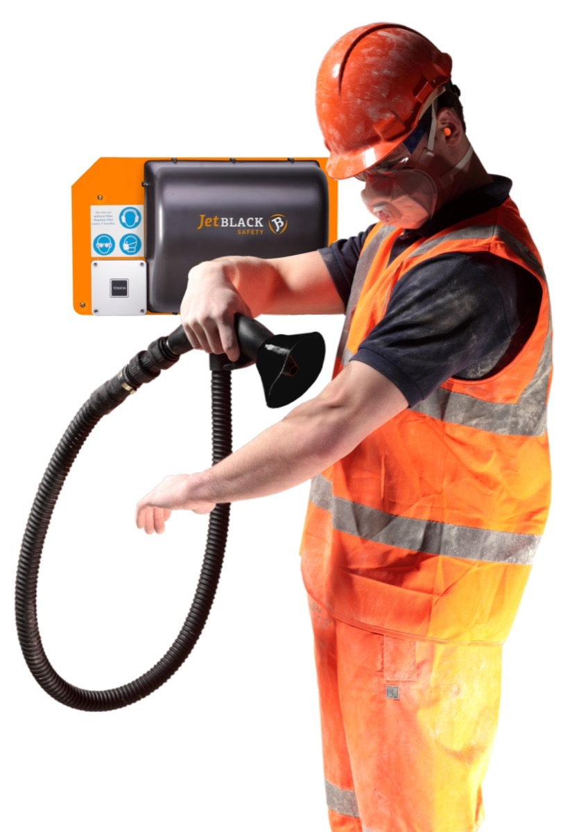 Man in PPE using the wall mounted JetBlack Safety Personnel Cleaning Station to blow dust off his arm