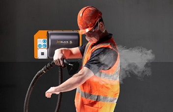 Man in PPE using a JetBlack Safety wall mounted personnel cleaning station to blow dust off his clothing